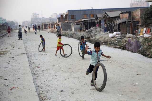 Children play with tyres along a street in Dhaka, Bangladesh on November 28, 2018. (Photo by Mohammad Ponir Hossain/Reuters)