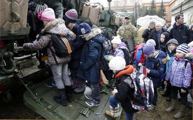 Children inspect a stryker armored vehicle during a stop of US military convoy in Prague, Czech Republic, Tuesday, March 31, 2015. (Photo by Petr David Josek/AP Photo)