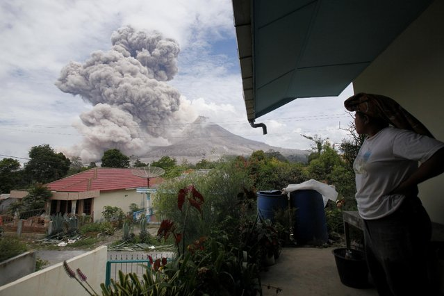 A villager watches as Mount Sinabung releases pyroclastic flows seen from Tiga Serangkai, North Sumatra, Indonesia, Wednesday, April 1, 2015. Mount Sinabung, among about 130 active volcanoes in Indonesia, has sporadically erupted since 2010 after being dormant for more then 400 years. (Photo by Binsar Bakkara/AP Photo)
