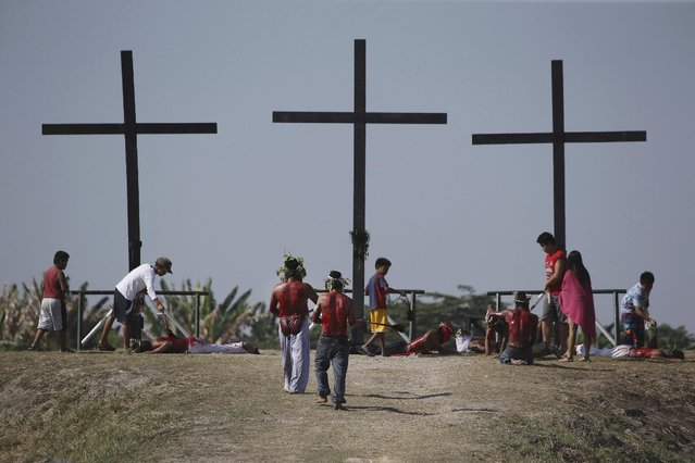 Hooded Filipino penitents walk towards the cross as they flagellate during Good Friday rituals to atone for sins on Friday, April 3, 2015 in Pampanga province, northern Philippines. (Photo by Aaron Favila/AP Photo)