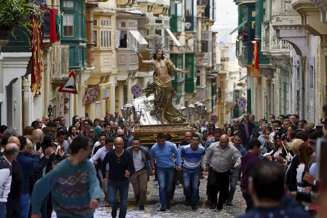 Worshippers run while carrying a statue of the Risen Christ  during an Easter Sunday procession in Cospicua, outside Valletta April 5, 2015. (Photo by Darrin Zammit Lupi/Reuters)