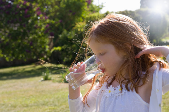 Girl drinking glass of water in backyard. (Photo by Henry Arden/Getty Images/Cultura RF)