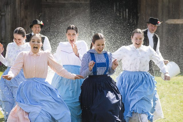 Dressed in folk costumes young women run away because young men pour water from their buckets on them as members of Nyirseg Dance Group perform Easter folk traditions in the Museum Village in Nyiregyhaza, 227 kms northeast of Budapest, Hungary, Monday, April 6, 2015. (Photo by Attila Balazs/AP Photo/MTI)