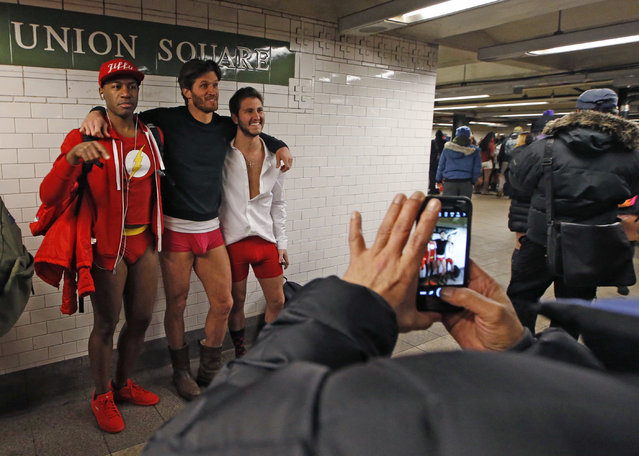 Three men pose in their underwear in front of a Union Square subway station sign during the 16th annual No Pants Subway Ride, Sunday, January 8, 2017, in New York. (Photo by Kathy Willens/AP Photo)