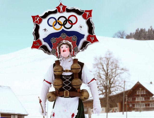 """A man dressed as a """"Chlaus"""", a figure that scares away evil spirits, carry round bells and cowbells as he walks through the snow-covered landscape during the traditional """"Sylvesterchlausen"""" near the northeastern village of Urnaesch, Switzerland January 13, 2017. (Photo by Arnd Wiegmann/Reuters)"""