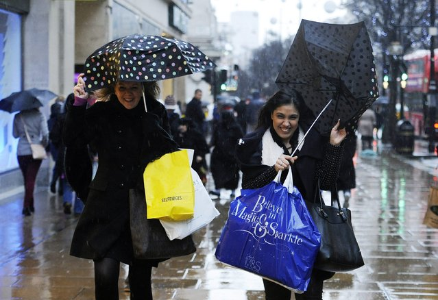 Women shoppers hang on tight to their umbrellas on Oxford Street in London's West End as they battle the rough weather on 23 December 2013. (Photo by Facundo Arrizabalaga/EPA)