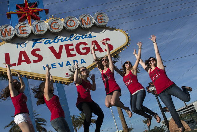 Women from Des Moines, Iowa have their photo taken in front of an iconic sign while celebrating a bachelor's party in Las Vegas, NV on February 20, 2016. (Photo by Linda Davidson/The Washington Post)