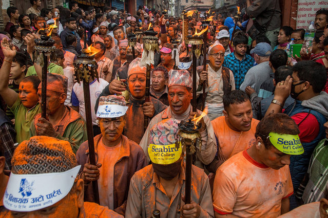 A group of devotees carry torches symbolising bringing in the spring sunshine that will nourish the crops during the Sindoor Jatra Festival on April 15, 2015 in Thimi, Nepal. (Photo by Omar Havana/Getty Images)