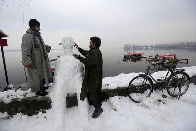 Kashmiri Muslim boat men make a snowman to attract customers after a fresh snowfall in Srinagar, India, Wednesday, January 1, 2014. Snowfall in the Indian portion of Kashmir has disrupted power supply, as well as air and road traffic between Srinagar and Jammu, the summer and winter capitals of India's Jammu-Kashmir state, according to news reports. (Photo by Dar Yasin/AP Photo)