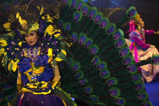 """A woman wearing an Indonesian colorful costume poses for photographs at the Indonesia stand during the """"FITUR"""" International Tourism Fair in Madrid, Friday, January 20, 2017. (Photo by Francisco Seco/AP Photo)"""