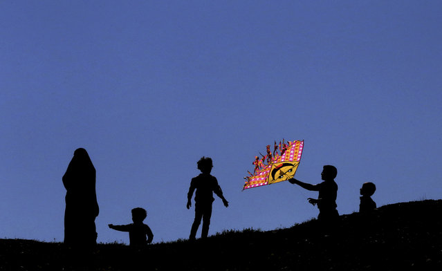 An Iranian boy flies a kite during the ancient festival of Sizdeh Bedar, an annual public picnic day on the 13th day of the Iranian new year, at the Pardisan Park in Tehran, Iran, Thursday, April 2, 2015. Iranians flocked to parks and wilderness on Thursday to mark the ancient festival, a legacy from pre-Islamic era, in the last day of Persian New Year holidays. (Photo by Vahid Salemi/AP Photo)