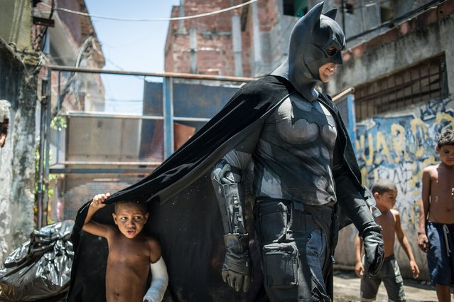 Children play around a man disguised as Batman at the Favela do Metro slum, area just near the Maracana stadium, in Rio de Janeiro, Brazil, on January 9, 2014. Families living in this shantytown within a stone's throw of Rio 's mythical Maracana stadium refuse to have their homes demolished as part of a project to renovate the district before the FIFA World Cup circus pitches camp in June. (Photo by Yasuyoshi Chiba/AFP Photo)