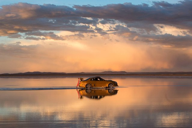The sky is reflected on the Uyuni Salt Flats as a car drives by in Uyuni, Bolivia,  Saturday, January 11, 2014. The motorcycles and quads of the Dakar Rally will race through parts of the Uyuni Salt Flats on Jan. 13, 2014. (Photo by Victor R. Caivano/AP Photo)