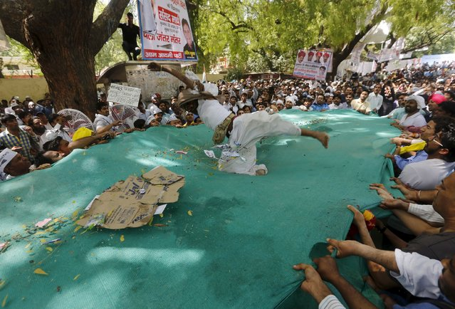 Protesters try to catch a farmer who hung himself from a tree in plastic sheets after his body was released by people during a rally organized by Aam Aadmi (Common Man) Party (AAP) in New Delhi April 22, 2015. (Photo by Adnan Abidi/Reuters)