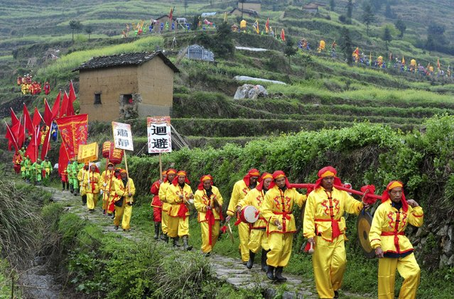 Villagers in traditional costumes play folk music instruments as they march among terraced crop fields to pray for good fortune, in Wuyi county, Zhejiang province April 10, 2015. (Photo by Reuters/Stringer)