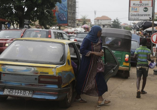 A woman disembarks from a taxi outside Kaporo market in Conakry, Guinea Monday, September 13, 2021. Guinea's longtime opposition leader says he welcomes the coup that deposed President Alpha Conde. But Cellou Dalein Diallo is calling on the junta leaders to create a transitional government and a timeline for elections as soon as possible. (Photo by Sunday Alamba/AP Photo)