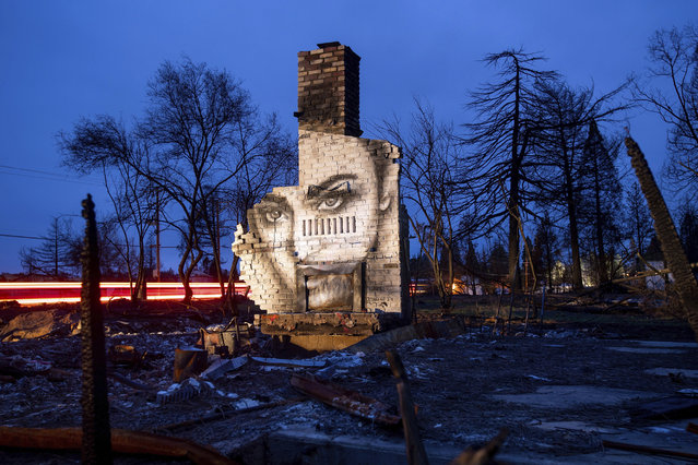 In this February 8, 2019, photo, a mural by artist Shane Grammer adorns the chimney of a residence leveled by the Camp Fire in Paradise, Calif. Grammer says he painted murals throughout the fire-ravaged town to convey hope in the midst of destruction. In the 100 days since a wildfire nearly burned the town of Paradise off the map, the long recovery is just starting. Work crews have been cutting down trees and clearing burned-out lots, but Paradise is mostly a ghost town where survivors still dig for keepsakes in the foundations of their homes. (Photo by Noah Berger/AP Photo)