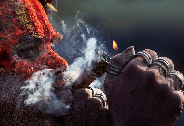 A sadhu, or holy man, smokes marijuana from a clay pipe at the Pashupati Temple in Kathmandu, Nepal, March 4, 2019, during celebrations marking the Hindu festival of Maha Shivaratri. (Photo by Narendra Shrestha/EPA/EFE/Rex Features/Shutterstock)