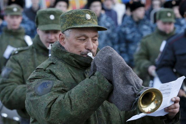 A member of a military orchestra warms a hand while playing a wind instrument during a rehearsal for the Victory Day festive march in the Siberian city of Krasnoyarsk, Russia, April 29, 2015. (Photo by Ilya Naymushin/Reuters)