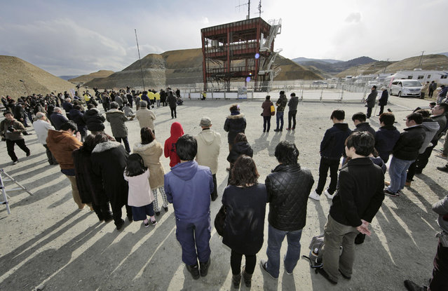 People observe a moment of silence at 2:46 p.m. for the victims of the 2011 earthquake and tsunami, in front of the skeletal remains of the former disaster prevention center in Minamisanriku, Miyagi prefecture, northern Japan Friday, March 11, 2016. Japanese gathered in Tokyo and along the country's ravaged northeast coast to observe a moment of silence at 2:46 p.m. (Photo by Yusuke Ogata/Kyodo News via AP Photo)