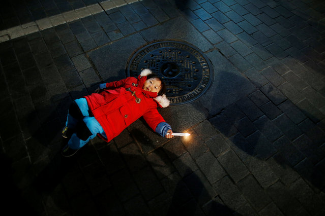 A girl holding a candle lies on a street during a protest demanding South Korean President Park Geun-hye's resignation in Seoul, South Korea, January 7, 2017. (Photo by Kim Hong-Ji/Reuters)