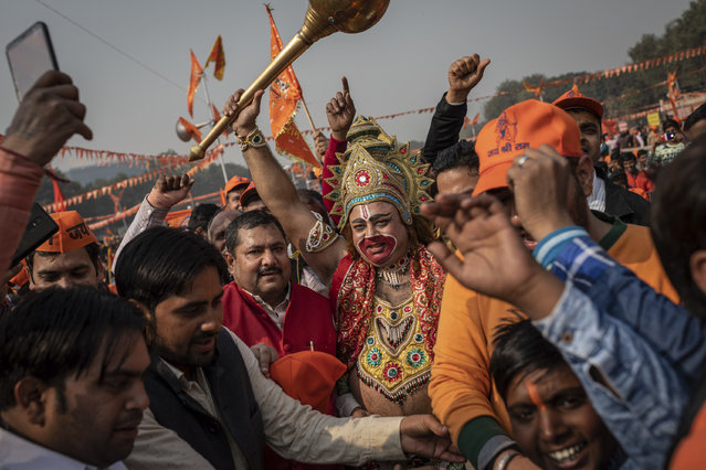 In this Sunday, December 9, 2018 photo, a supporter of the Hindu nationalist political group Vishwa Hindu Parishad is dressed as the Hindu deity Hanuman during a rally in New Delhi, India. Tens of thousands of worshippers gathered in India's capital to demand construction of a Hindu temple on the ruins of a disputed 16th century mosque in northern Indian city of Ayodhya. (Photo by Bernat Armangue/AP Photo)