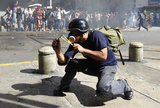 An opposition demonstrator aims a slingshot at police during a protest against Venezuela's President Nicolas Maduro's government in Caracas February 12, 2014. A demonstrator (not pictured) was killed during the anti-government rally in Caracas on Wednesday, Reuters witnesses said. (Photo by Carlos Garcia Rawlins/Reuters)