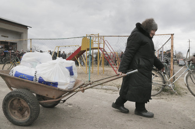 A elderly woman pulls a barrow with humanitarian aid distribution by an EU humanitarian program in Semonovka, Eastern Ukraine, Thursday, March 17, 2016. Premier Urgence Internationale (PUI) opened its mission in Ukraine in the beginning of 2015 after identification of crucial humanitarian needs in Eastern Ukraine linked to the intensification of the military conflict. (Photo by Efrem Lukatsky/AP Photo)