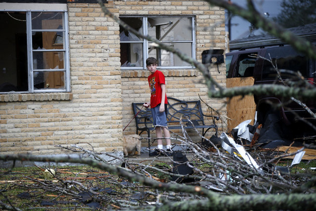 A boy holds his dog after a tornado tore through the New Orleans East neighborhood in New Orleans, Tuesday, February 7, 2017. (Photo by Gerald Herbert/AP Photo)