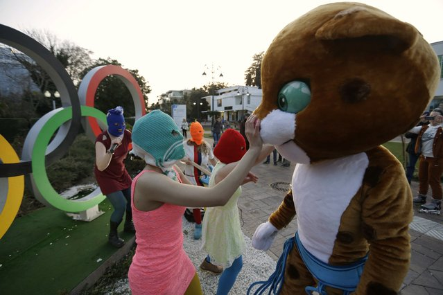 p*ssy Riot member Nadezhda Tolokonnikova in the aqua balaclava, left, interacts with an Olympic mascot while the group perform next to the Olympic rings in Sochi, Russia, on Wednesday, February 19, 2014. Cossack militia attacked the punk group with horsewhips earlier in the day as the artists – who have feuded with Vladmir Putin's government for years – tried to perform under a sign advertising the Sochi Olympics. (Photo by David Goldman/AP Photo)