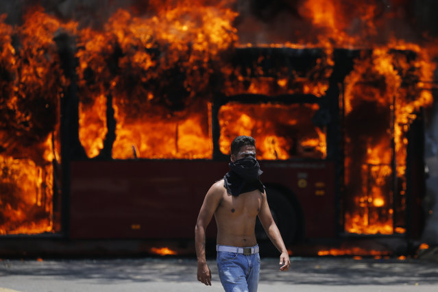 An anti-government protester walks near a bus that was set on fire by opponents of Venezuela's President Nicolas Maduro during clashes between rebel and loyalist soldiers in Caracas, Venezuela, Tuesday, April 30, 2019. (Photo by Fernando Llano/AP Photo)