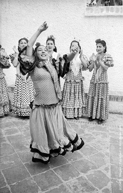 Andalusian gypsies in traditional dress dancing the flamenco