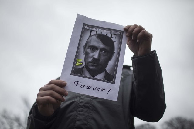 A protester holds a modified magazine cover depicting Russian President Vladimir Putin during a protest march in Kharkiv, on March 2, 2014. Ukraine's premier said on Sunday that the nation was on the brink of disaster. (Photo by Uriel Sinai/The New York Times)