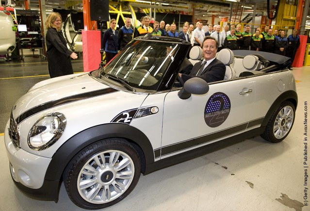 British Prime Minister David Cameron, beside BMW group management member for production Frank-Peter Arndt, drives the two millionth MINI off the production line