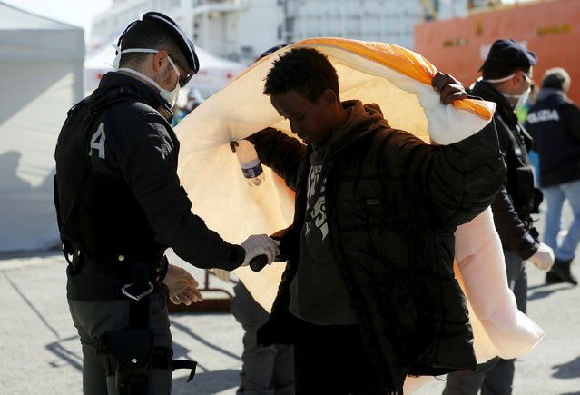 A migrant is inspected by policemen after disembarking from the Norwegian vessel Siem Pilot at Pozzallo's harbour, Italy, March 29, 2016. (Photo by Antonio Parrinello/Reuters)