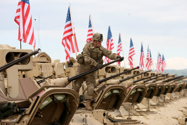 """A US soldier prepares an armoured vehicle for the official opening ceremony of the joint US-Georgia military exercise """"Noble Partner 2015"""" at the military base of Vaziani outside Tbilisi, Georgia, 11 May 2015. Exercise Noble Partner is a bilateral effort focused on enhancing US and Georgian NATO Response Force interoperability in the context of military-to-military relationships. (Photo by Zurab Kurtsikidze/EPA)"""