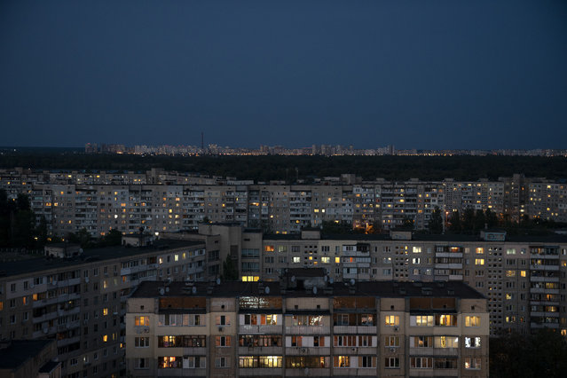In this August 21, 2018 photo, buildings are illuminated at dusk In Kiev, Ukraine. (Photo by Felipe Dana/AP Photo)