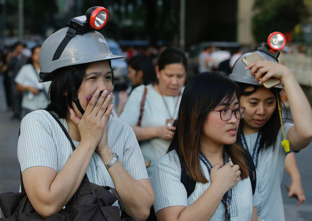 In this April 22, 2019, file photo, wearing protective helmets, employees evacuate their office building following an earthquake in Manila, Philippines. (Photo by Aaron Favila/AP Photo/File)