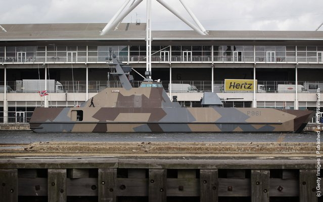 A sailor walks on the deck of a Skjold class missile fast patrol of the Royal Norwegian Navy at anchor next to the ExCeL exhibition centre