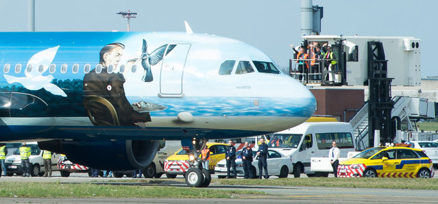 Airport workers wave as a Brussels Airlines plane taxis towards the runway at Brussels Airport, in Zaventem, Belgium, Sunday, April 3, 2016. Under extra security, three Brussels Airlines flights, the first for Faro in Portugal, were scheduled to leave Sunday from an airport that is used to handling about 600 flights a day. (Photo by Benoit Doppagne/Pool Photo via AP Photo)