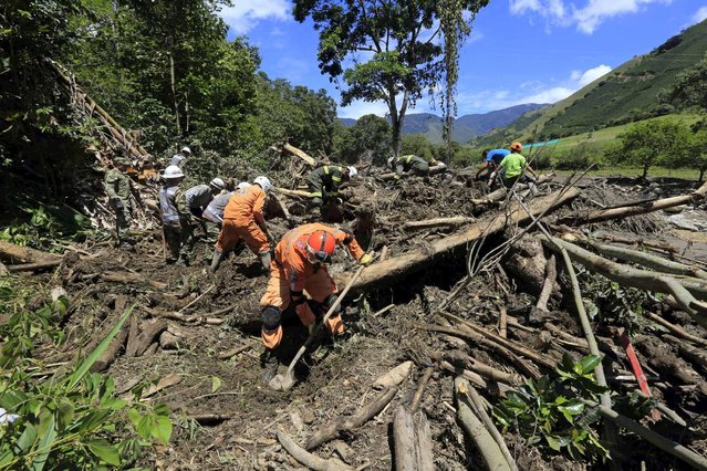 Rescue workers search for the bodies of victims in a landslide that sent mud and water crashing onto homes close to the municipality of Salgar in Antioquia department, Colombia May 19, 2015. (Photo by Jose Miguel Gomez/Reuters)