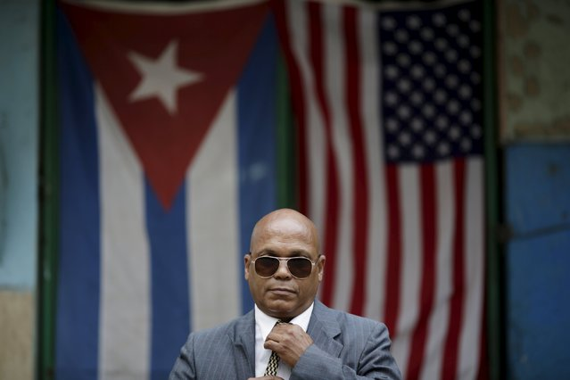 "Lazaro Roger, 56, poses for a photograph in front of the Cuban and U.S. flags in Havana, March 23, 2016. Regarding Obama's historic visit to the island, Roger said ""This is grand, historical and very positive that the USA have realized after all these years that the embargo is not worth it"". (Photo by Ueslei Marcelino/Reuters)"
