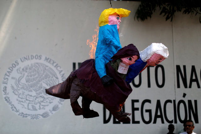 Activists burn a pinata depicting U.S. President Donald Trump, Mexican President Andres Manuel Lopez Obrador, Secretary of Government Olga Sanchez Cordero, and Federal Immigration Delegate Yadira de los Santos during a protest outside the premises of the National Migration Institute (INM) in Tapachula, Mexico April 6, 2019. (Photo by Jose Cabezas/Reuters)