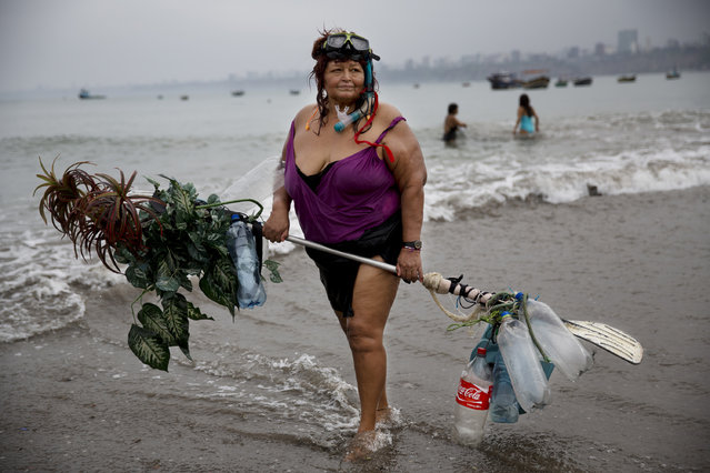 In this May 7, 2015 photo, Graciela Meneses poses for a picture on Fishermen's Beach, holding her self-made float, decorated with fake, plastic plants, after swimming in the Pacific Ocean in Lima, Peru. Graciela, 67, says she lost 39 kilograms (85 pounds) by exercising in the sea. (Photo by Rodrigo Abd/AP Photo)