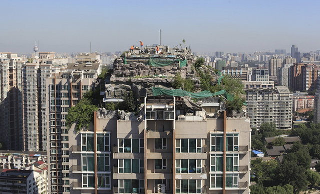 Workers demolish a privately-built villa, surrounded by imitation rocks, on the rooftop of a 26-storey residential building in Beijing, China August 26, 2013. (Photo by Reuters/Stringer)