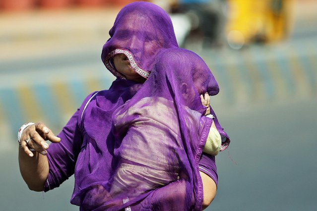 An Indian woman carrying a child uses a part of her sari to shield themselves from sun on a hot summer day in Hyderabad, India, Tuesday, May 28, 2019. The city has been experiencing extreme heat conditions with temperature recorded at 43 degrees Celsius (109.4 Fahrenheit) on Tuesday. (Photo by Mahesh Kumar A./AP Photo)