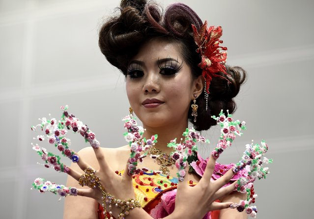 A model shows nail-art during a hairstyling and make-up competition in Kuala Lumpur on May 18, 2015. Professional hair-dressers and make-up stylists from 14 countries participated in the event showcasing creative hairdos, make-up and nail-art. (Photo by Manan Vatsyayana/AFP Photo)