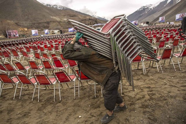 A supporter of Afghan presidential candidate Zalmai Rassoul carries chairs as he prepares for an election rally in Panshir, northern Afghanistan, March 28, 2014. (Photo by Zohra Bensemra/Reuters)