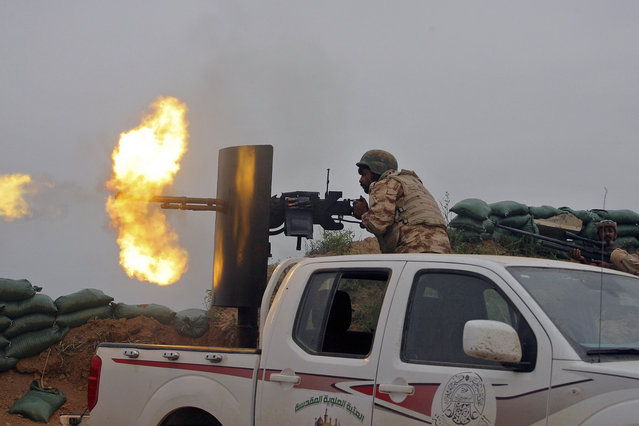 Iraqi security forces and allied Popular Mobilization forces fire towards positions in the Islamic State-held town of Besher, during a military operation to regain control of the small town outside the oil-rich city of Kirkuk, Iraq, 180 miles (290 kilometers) north of Baghdad, Sunday, April 10, 2016. (Photo by Anmar Khalil/AP Photo)