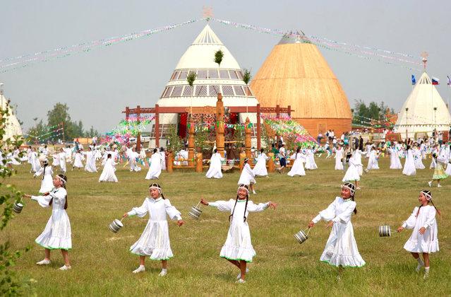 People in ethnic costumes take part in celebrations of the traditional Yakut New Year festival Ysyakh Tuimaady at the Us Khatyn ethnographic park near Yakutsk, Russia on June 29, 2019. (Photo by Svetlana Pavlova/TASS)